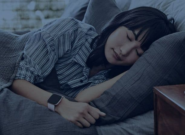 Fitbit woman sleeping with Fitbit tracking sleep stages