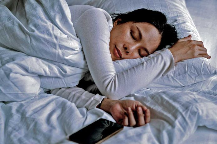 woman sleeping with phone next to her
